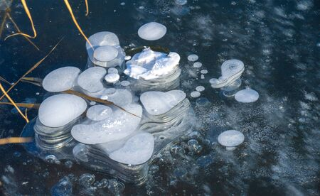 There is frost on the street, ice on the river, ice bubbles stuck in ice, unusually colorful ice architecture