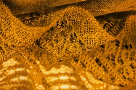 Background, texture, pattern, yellow lace fabric, thin open fabric, usually made of cotton or silk, made using loops, twisting or knitting threads in patterns 免版税图像