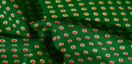 Texture background, pattern,  green silk fabric with red polka dots. Light and silky-soft satin pendant is perfect for your design, online projects. It is also perfect for screensavers and wallpapers