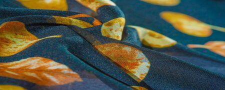 Texture, background, pattern, silk fabric, blue with a print of yellow autumn leaves. Imagens