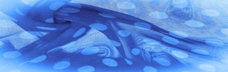 Background texture, decorative ornament, blue polka-dot silk fabric, round dots on fabric that have a shape or approximately resemble a circle or cylinder.