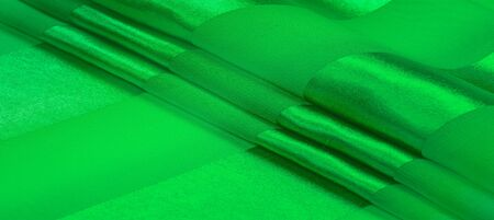 Texture, background, green silk striped fabric with a metallic sheen. If you have a bad mood, this fabric will lift it to unprecedented heights. Your project will be successful. Banque d'images