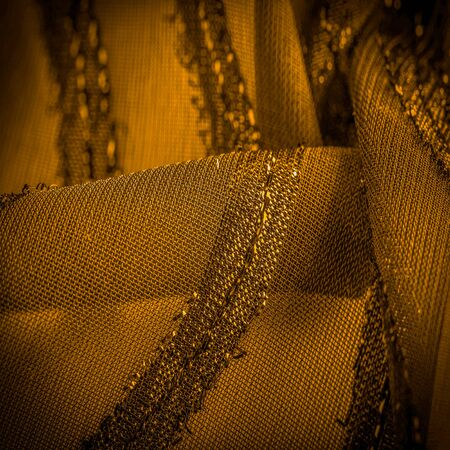 ornament of the decor, the fabric is transparent mustard yellow with brightly congenital stripes, the material allowing the light to pass through it so that the objects behind are clearly visible Imagens