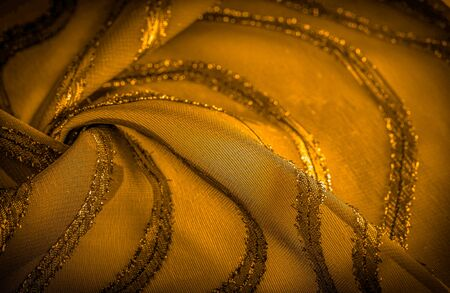 ornament of the decor, the fabric is transparent mustard yellow with brightly congenital stripes, the material allowing the light to pass through it so that the objects behind are clearly visible