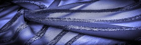 texture  background image, the fabric is transparent deep blue with brightly congenital stripes, the material allowing the light to pass through it so that the objects behind are clearly visible. Imagens