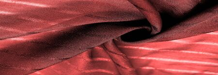 Texture, background, pattern, simple red fabric with lines. The lines formed by the extraction of the thread,