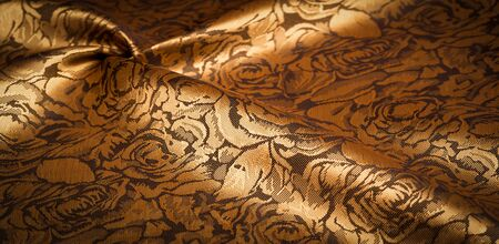 embossed pattern, composite textile, silk fabric of yellow, gold color, with a floral pattern, unusually pleasant visual sensations: slippery, coolness, softness; beautiful appearance, unique shine;