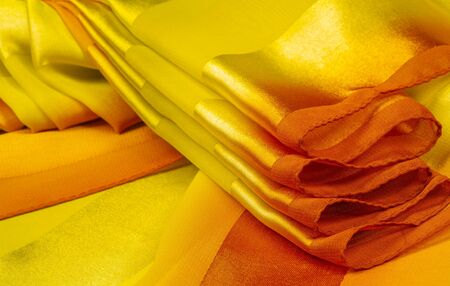 Texture, background, yellow silk striped fabric with a metallic sheen. If you have a bad mood, this fabric will lift it to unprecedented heights. Your project will be successful. Archivio Fotografico