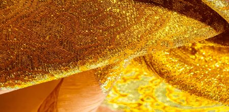 Texture background, pattern. fabric; yellow gold brocade. Organza brocade fabric - shepherd, with a crunchy palm. It has a large yarn-dyed flower embroidered pattern throughout.