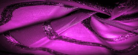 the ornament of the decor, the transparent fabric is purple-red with brightly innate stripes, the material allowing the light to pass through it so that the objects behind are clearly visible.
