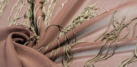 Background texture of silk fabric. This is a natural brown scarf, this beautiful nylon satin made of artificial silk with a clear hand and a wonderful sheen is perfect for your projects. 版權商用圖片