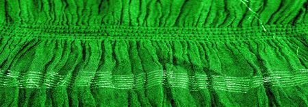 Background texture, ornament decor, emerald green centered corrugated fabric, fabric with parallel or diagonal folds of serrated folds; products from such a fabric.