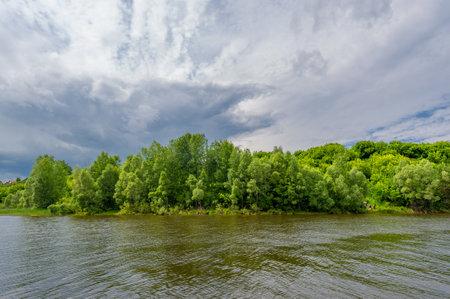 summer photo, powerful thunderclouds, blue sky, dark sharp water, tourist walk along the Kama River