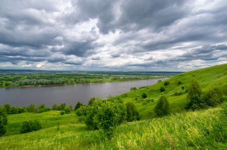 Summer landscape, a large full-flowing river, meadow flowers on the banks of the river, mighty clouds in the sky, a tourist walk along the Kama River Standard-Bild