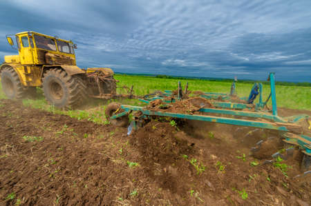 Spring photography, landscape with agricultural machinery, a tractor plows the land, plows a field, birds fly over arable land Stock fotó
