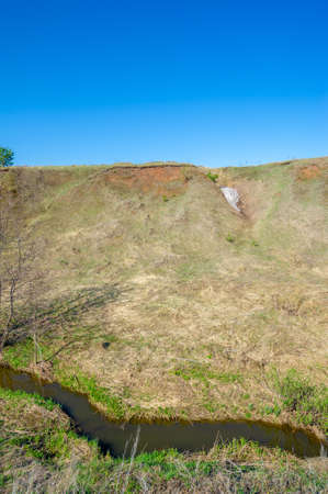Photographs of a landscape, stream, Spring, Gully is a relief created by running water, rapidly collapsing into the soil, usually on a hillside. Gullies resemble large ditches or small valleys, Banco de Imagens
