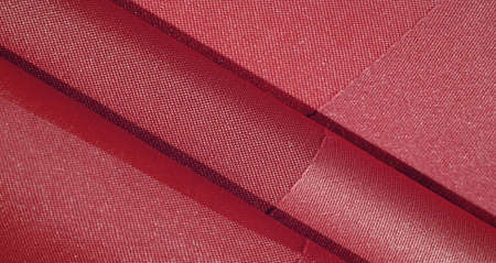 The silk fabric is ruby red. texture of colored silk fabric - can be used as a background Stock Photo