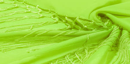 Green silk shawl with fringe at the edge of the fabric. This is a common type of tie. Warm green on a white background. Template Standard-Bild - 161768584