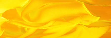 Yellow silk organza with wavy piping. Border around the edge of the fabric. Abstract background. texture pattern. Silk organza has a delicate open weave. Wave background. Copy space