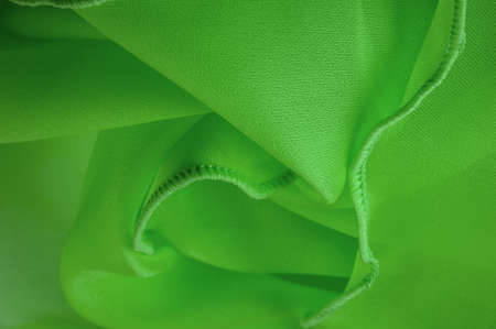 Green silk organza with wavy piping. Border around the edge of the fabric. Abstract background. texture pattern. Silk organza has a delicate open weave. Wave background. Copy space