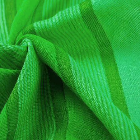 Texture. Background. Silk fabric green fresh color, of the color between blue and yellow in the spectrum; colored like grass or emeralds.