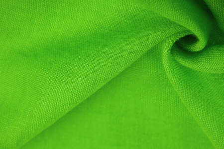 Green silk fabric. Grunge surface texture with fine grains, green satin texture, which is an emerald fabric, silk panorama, with a beautiful soft natural blur pattern.