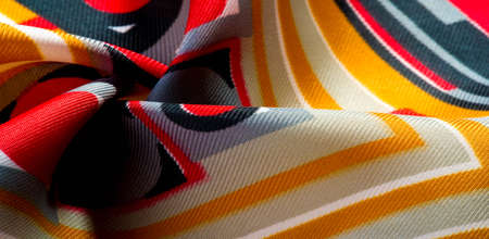 Silk fabric of geometric abstract shapes from lines. Red yellow gray brown colors print from line pattern texture. Stock Photo
