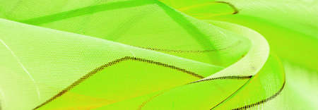 fine knitted fabric - light transparent, green, white and yellow geometric colors, similar to a veil of fine rayon silk. organza pattern. Texture. Background