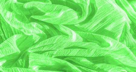 Silk fabric. Green wrinkled fabric texture. Green wrinkled, wavy surface texture. Close-up, soft focus. background, pattern