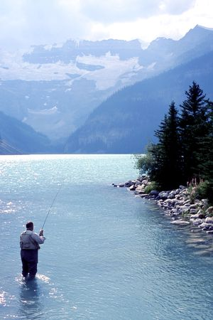 volar: El hombre pesca con mosca en el lago glaciar  Foto de archivo