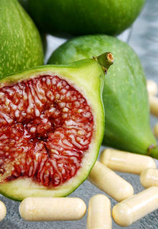 perishable: display of fresh green figs and vitamin supplements