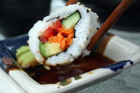 crab pots: dipping sushi california roll in soya sauce