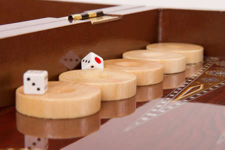 battle plan: Chips and dices on backgammon table.