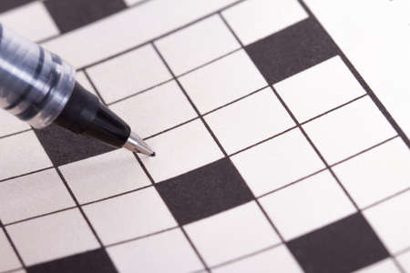 Close up of blank square crossword puzzle for solution with black pen.