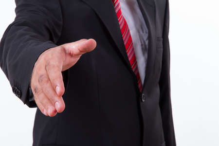 Businessman extends hand to shake or helping, isolated on white. photo