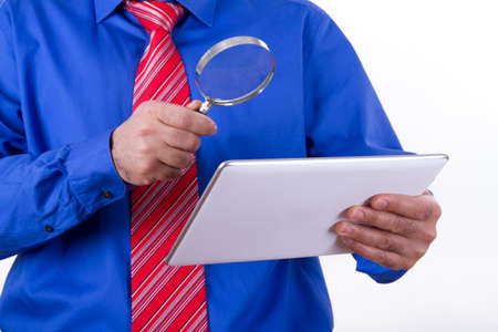 multi touch: Businessman with red tie and blue shirt holding magnifying glass to tablet, isolated on white background.