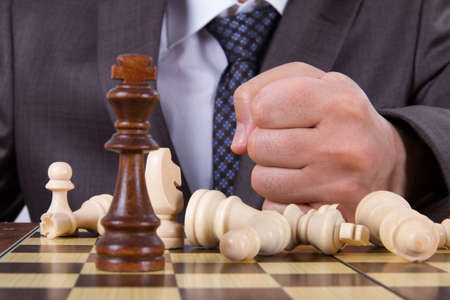 defeated: Businessman hits his punch to chess board, defeated concept.