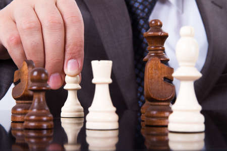 Businessman holding pawn for move on dark reflective table.