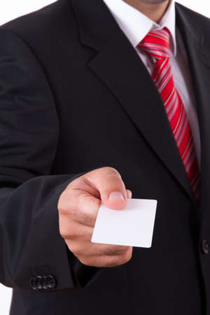 Businessman in dark suit and white shirt with red striped tie, shows white blank business card with space. Stock Photo