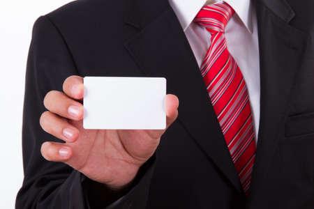 hand business card: Uomo d'affari in abito scuro e camicia bianca con cravatta a righe rosse, mostra bianco biglietto vuoto con lo spazio.