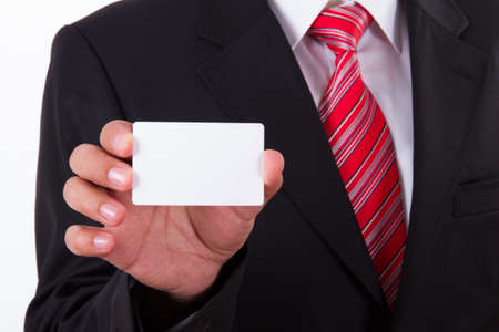 Zakenman in donker pak en wit overhemd met rode gestreepte band, toont wit blanco visitekaartje met ruimte. Stockfoto
