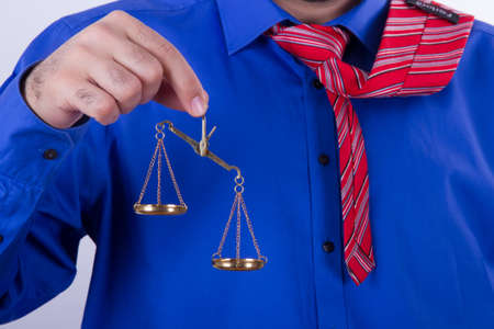 unbalanced: Businessman with red tie and blue shirt holding golden scales unbalanced, isolated on white background. Stock Photo