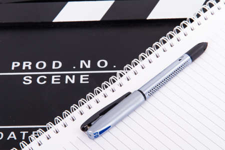 Black cinema clapper board and notebook for scenario with pen, isolated on white background. photo