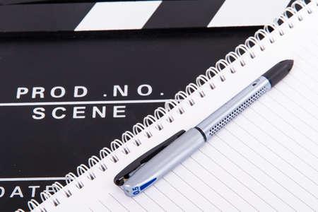 Zwart bioscoop klepel boord en notebook voor scenario met pen, geïsoleerd op een witte achtergrond.