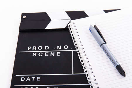 script: Black cinema clapper board and notebook for scenario with pen, isolated on white background.