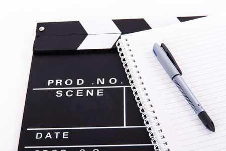 Zwarte bioscoop klepel boord en notebook voor scenario met pen, geïsoleerd op een witte achtergrond.