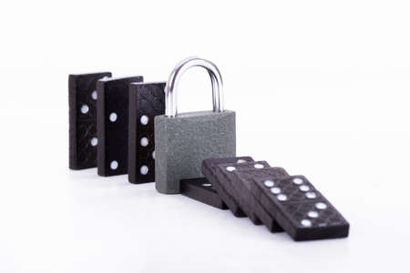 damage control: Damage control of black dominoes with padlock for security, isolated on white background.
