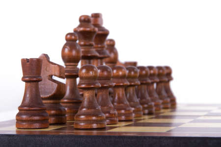 Chess board with starting positions aligned dark wooden chess pieces, isolated on white background. photo