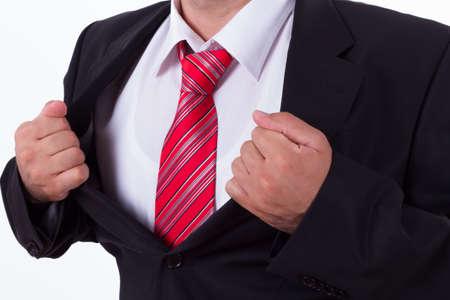 Businessman showing superhero suit, isolated on white. photo
