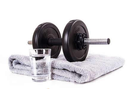 검은 체육관 바 벨, 디스크, 파란색 수건 및 흰색 배경에 절연 물 한잔 아령.